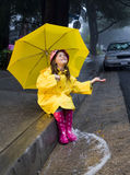 Young caucasian girl playing in the rain. Young caucasian girl with brown hair playing in the rain with yellow umbrella and raincoat with pink rainboots Royalty Free Stock Images