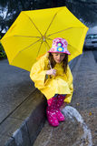 Young caucasian girl playing in the rain. Young caucasian girl with brown hair playing in the rain with yellow umbrella and raincoat with pink rainboots Stock Photos
