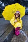 Young caucasian girl playing in the rain. Young caucasian girl with brown hair playing in the rain with yellow umbrella and raincoat with pink rainboots Stock Photography