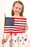 Young caucasian girl holding an American Flag. A young Caucasian girl in a polka dot dress holding an American Flag Stock Photo