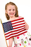 Young caucasian girl holding an American Flag. A young Caucasian girl in a polka dot dress holding an American Flag Stock Images