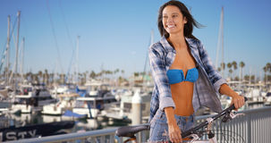 Young Caucasian girl rides her bike next to the marina Royalty Free Stock Images