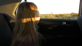 Young caucasian girl riding by car. Slow motion. Focus to outside of cars window to field and rural scene. Autumn sunset. Unfocused foreground stock video