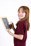 Young school girl writing on chalk board. A young Caucasian girl, in a school uniform polo shirt, writing on a small chalk board with a large piece of white Royalty Free Stock Images