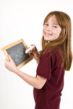 Young school girl writing on chalk board. A young Caucasian girl, in a school uniform polo shirt, writing on a small chalk board with a large piece of white Royalty Free Stock Photography