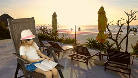 Young caucasian girl sitting on armchair and reading book. Sunset on sea. Long chair and umbrella. Have same clip with stock video footage