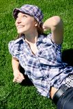 Young caucasian girl sitting on the green grass Royalty Free Stock Photo