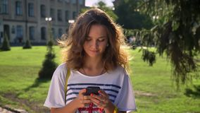 Young Caucasian girl is standing in a park and is using a smartphone, thinking, university in the background