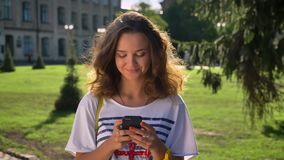 Young Caucasian girl is standing in a park and is using a smartphone, typing, university in the background stock footage