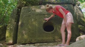 Young caucasian girl standing and touching an ancient dolmen stock video