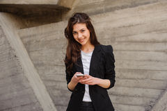 Young Caucasian Girl Text Messaging Looking At The Camera. Royalty Free Stock Image
