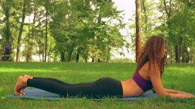 Young caucasian girl trains outdoor. Brunette woman doing extended puppy pose in park sitting on a blue mat. lady with long curly hair trains outdoors. nature stock footage