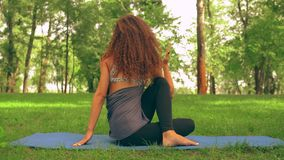 Young caucasian girl trains yoga outdoor. Brunette woman doing half lord of the fishes pose in park sitting on a blue mat. lady with long curly hair trains stock footage