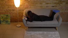 Young caucasian girl with wavy hair lying on sofa and watching with concentration into tablet in cosy home atmosphere. Young caucasian girl with wavy hair lying stock video footage