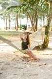 Young caucasian girl wearing green dress sitting on wicker hammock with sand and palms in background. stock image