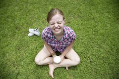 Young caucasian girl woman sitting on the grass, smiling royalty free stock photography