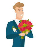 Young caucasian groom with bridal bouquet. Royalty Free Stock Photography