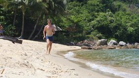 Young caucasian guy wearing shades and summer shorts running on the beach.
