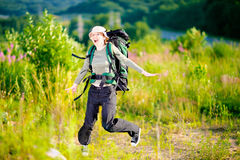 Young caucasian hiking woman with backpack happily jumping. Looking at camera. Royalty Free Stock Photography