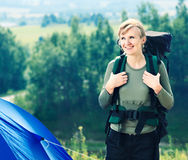 Young caucasian hiking woman with backpack standing near tent. Stock Photography