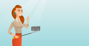 Young caucasian hipster man making selfie. Caucasian business woman making selfie with a selfie-stick. Smiling woman taking photo with a cellphone. Young woman Stock Image