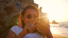 Young caucasian hipster woman swinging in hammock at the beach near the sea against stunning golden sunset and using stock video
