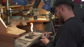 Jeweler sets fire on gas torch. Young caucasian jeweler setting fire on gas torch. Bearded man winding power knob on burner. Jewelry specialist beginning to melt stock photography