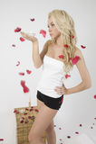 Young caucasian lady blowing petals Royalty Free Stock Photos