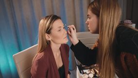 A young Caucasian make-up artist draws and shapes the eyebrows with a pencil on the face of a Caucasian blonde model. Against the background of a lot of stock video footage