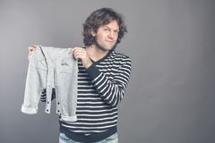 Young caucasian male boasting about new stylish baby clothes for his son holding in hands and demonstrating grey pants stock image