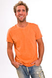 Young caucasian male in a bright orange t-shirt and jeans. A young blonde, Caucasian, male with blue eyes in a bright orange t-shirt and jeans Stock Image