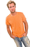 Young caucasian male in a bright orange t-shirt and jeans Stock Images