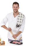 Young  caucasian male cook with, preparing steak Royalty Free Stock Photos