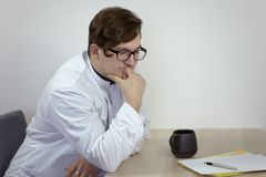 Young caucasian male doctor in a white outfit sits thoughtful, holding his chin, with cup of tea or coffee and papers on the table stock photos