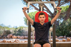 Young caucasian male exercising upper body on gym machine outdoors. Young caucasian male exercising upper body on gym machine outdoors surrounded by trees Stock Photography