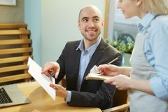 Businessman ordering lunch in cafe. Young Caucasian male guest sitting at cafe table with menu, ordering meal and smiling to waitress cheerfully Stock Photos