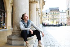 Young caucasian male tourist sitting near columns on Main Square in Krakow, Poland. Young caucasian male tourist wearing casual clothes and sitting near columns Stock Photo