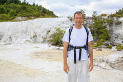 Young caucasian man with back carrier, Orakei Korako in NZ. Royalty Free Stock Photos