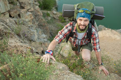 Young caucasian man with backpack climbing the Royalty Free Stock Photo