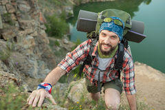 Young caucasian man with backpack climbing the Stock Photography