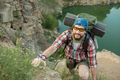 Young caucasian man with backpack climbing the Stock Photos