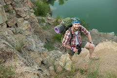 Young caucasian man with backpack climbing the Royalty Free Stock Photography