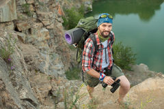 Young caucasian man with backpack climbing the Royalty Free Stock Images