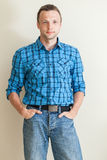 Young Caucasian man in blue shirt and jeans Stock Photography