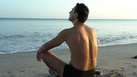Young caucasian man relaxing on the beach near calm sea, close-up of hands, gyan mudra and lotus position. Sunrise stock video