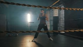 Young caucasian man boxing on the ring with yellow ropes in industrial gym. Light-weight boxer training. Fighting the shadow slow motion stock video footage