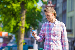 Young caucasian man with cell phone in european. Young caucasian man talking by cell phone at old streets in european city, Amsterdam, Holland Stock Images