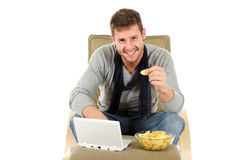 Young caucasian man, chips and netbook Stock Images