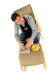 Young caucasian man, chips and netbook Royalty Free Stock Photography