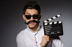 Young caucasian man with clapperboard against gray Royalty Free Stock Photo